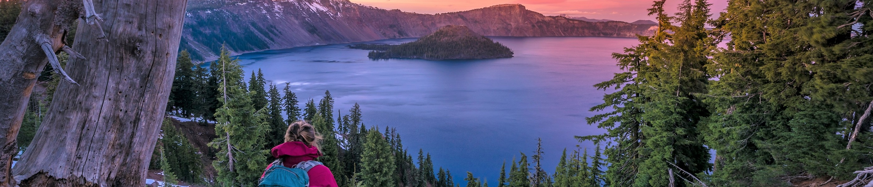 A hiker taking in Crater Lake's breathtaking beauty
