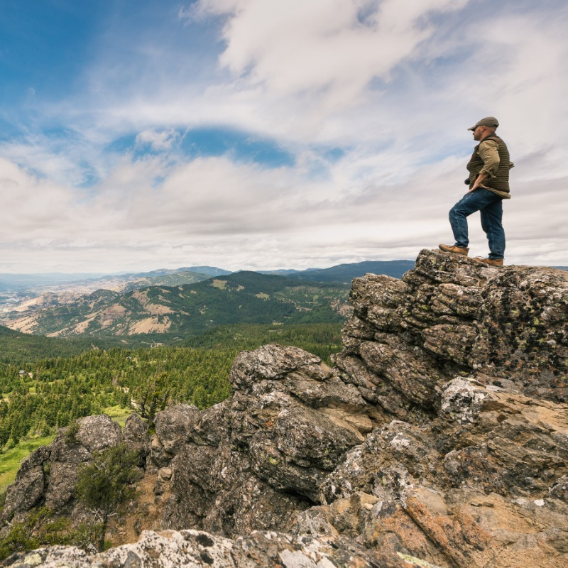 A hiker taking in the view on top of RoxyAnn Peak